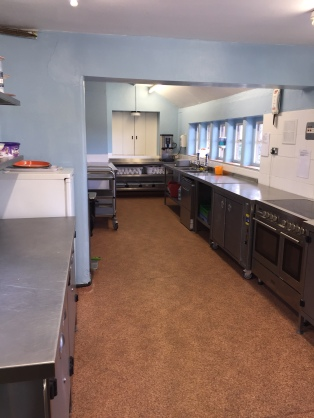 Kitchen area with serving hatch to smaller side room